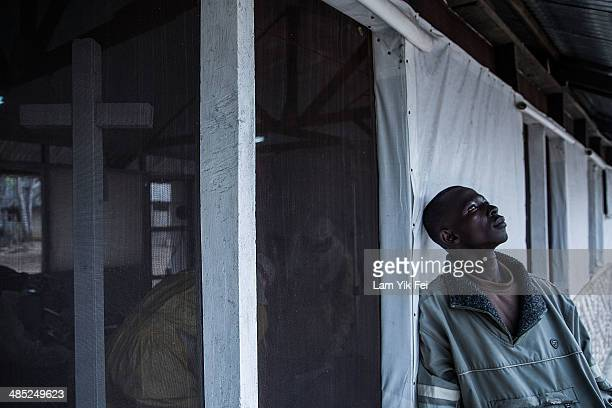A father waits outside the Lassa isolation ward as his daughter is receiving treatment inside at Gondama Referral Centre on March 6 2014 in Bo...