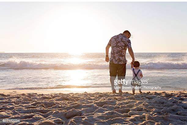a father waling towards the ocean at sunset holding his toddler daughter's hand. - rabbit beach stock photos and pictures