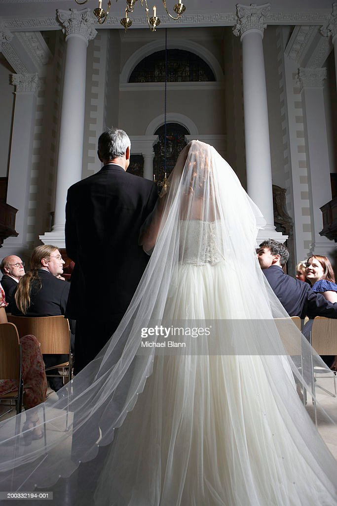 Father walking bride down church aisle, rear view : Stock Photo