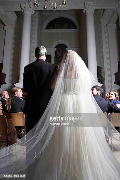 Father walking bride down church aisle, rear view