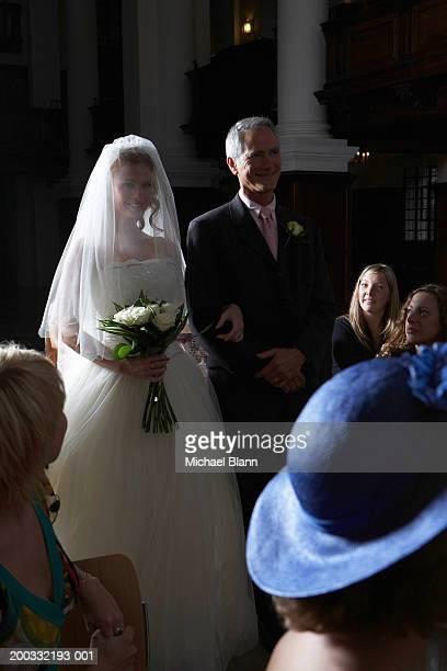 Father walking bride down church aisle, smiling