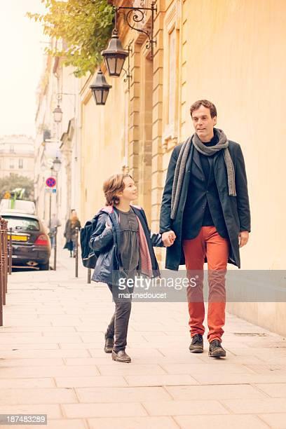 Father walking child to school in european street.