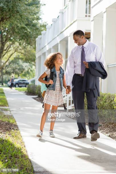 Father walking daughter to school