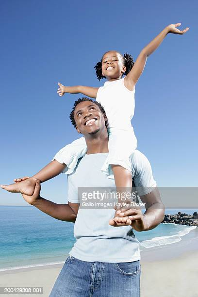 Father walking on beach carrying daughter (5-7) on shoulders, smiling