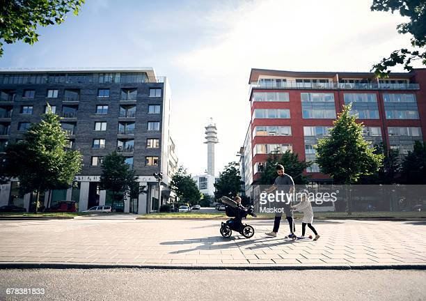 father walking with baby stroller looking at daughter riding push scooter in city - high street stock pictures, royalty-free photos & images