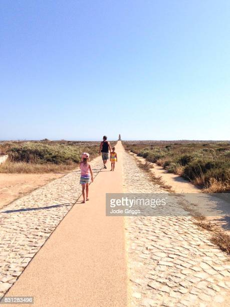 father walking with children around the sagres fortress - sagres stock pictures, royalty-free photos & images