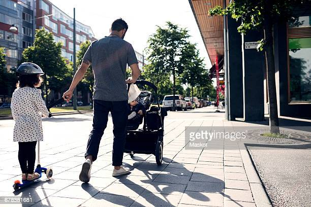 Father walking with children on sidewalk in city during sunny day