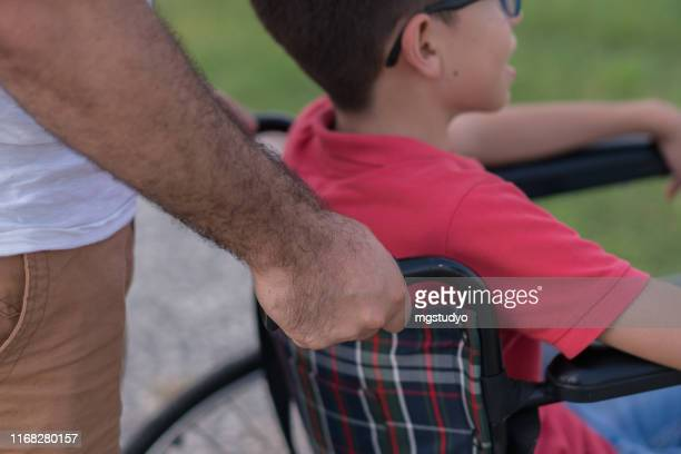 father walking with disabled son in park - autismo foto e immagini stock