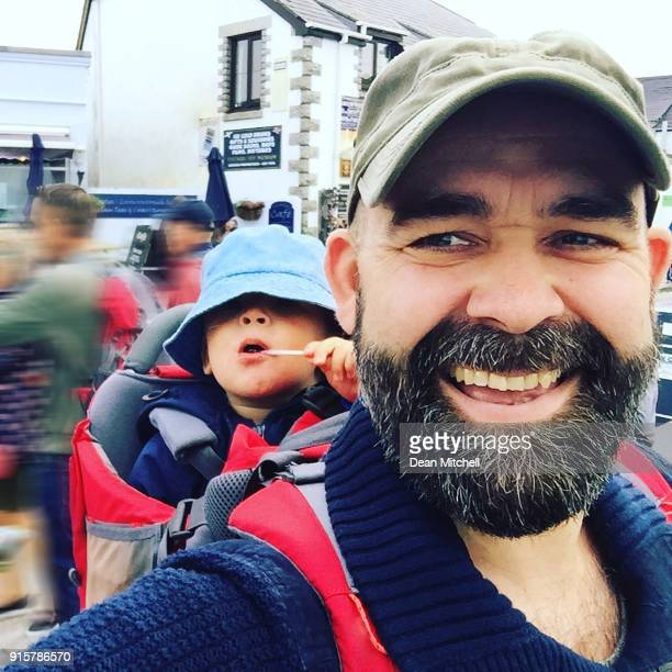 father walking with little boy on his back - taken on mobile device stock photos and pictures