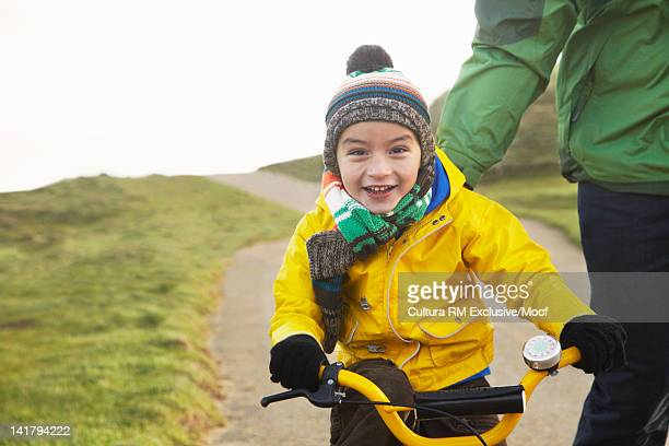 Father walking with son on bicycle