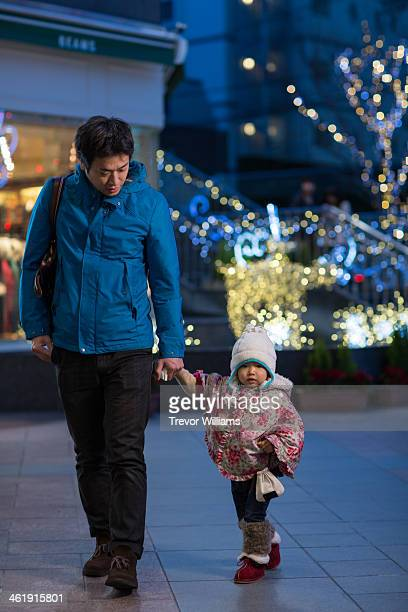 Father walking with toddler daughter at night