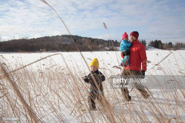 Father walking with two sons in snow covered landscape