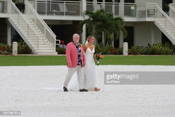 Father walks the bride along the beach during a beach wedding on the beautiful San Marco Beach on Marco Island Florida USA on August 30 2018