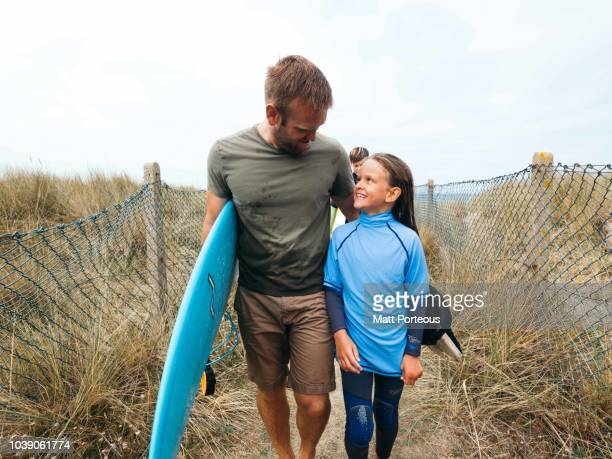 Father walks with daughter after surf