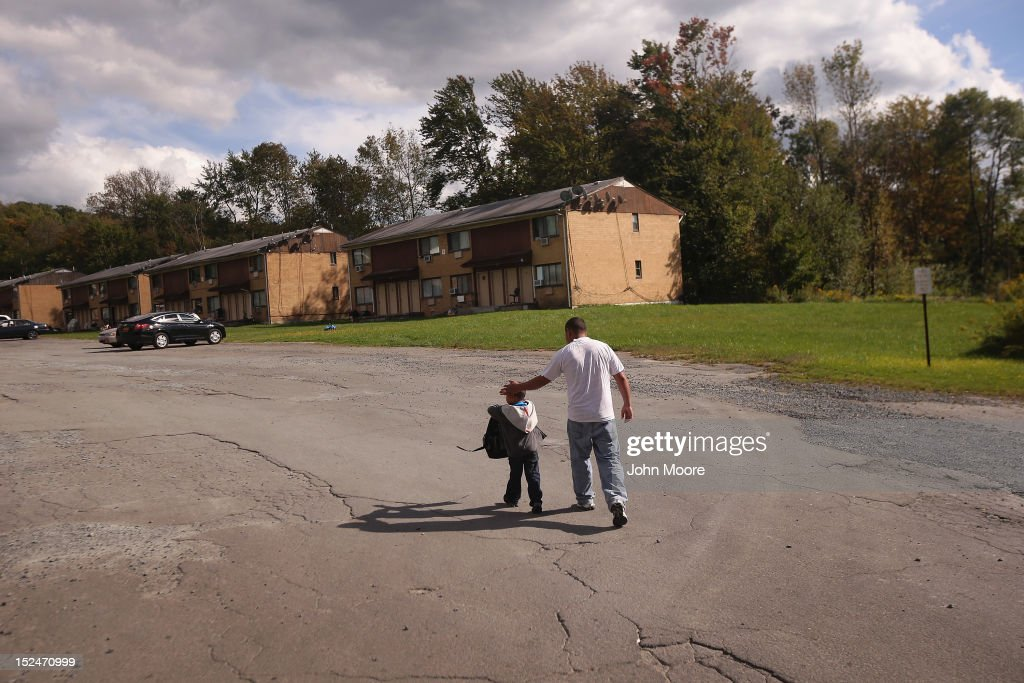 A father walks with his son after a school bus brought the child home from the federally-funded Head Start school on September 20, 2012 in Woodbourne, New York. The school provides early education, nutrition and health services to 311 children from birth through age 5 from low-income families in Sullivan County, one of the poorest counties in the state of New York. The county Head Start Program was expanded with a $1 million grant from President Obama's 2009 stimulus bill, the American Recovery and Reinvestment Act. Head Start, administered by the U.S. Department of Health and Human Services, is the longest-running early education program for children of low-income families in the United States.