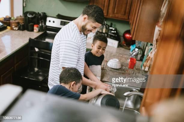 父は息子とキッチンで皿を洗い