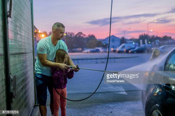 Father washing car with daughter