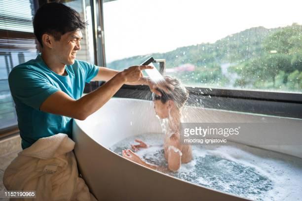 padre lavar hijos pelo en la bañera - chicos desnudos fotografías e imágenes de stock
