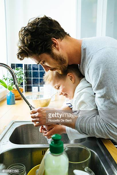 father washing sons hands in kitchen sink after cooking together - kin in de hand stock pictures, royalty-free photos & images