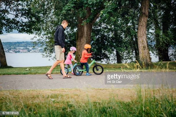 Father watching daughter and son riding bicycles