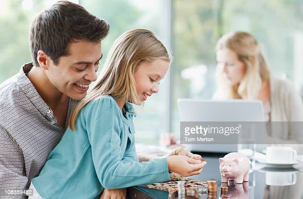 father watching daughter count coins - piggy bank stock photos and pictures