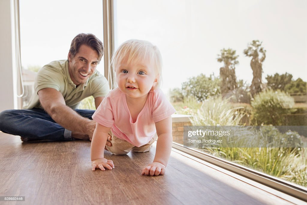Father watching daughter (12-23 months) crawling on floor : Stockfoto