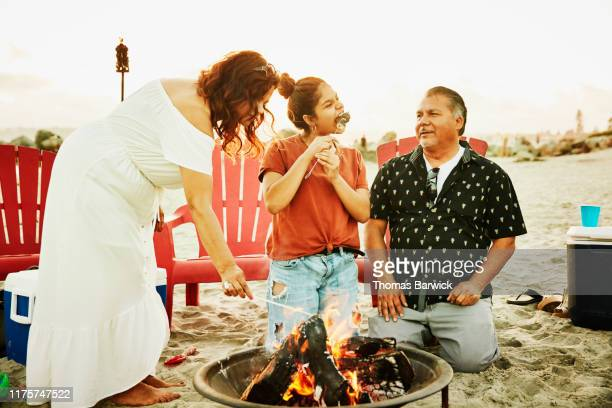 father watching daughter eat marshmallow after roasting over beach fire - disruptaging foto e immagini stock