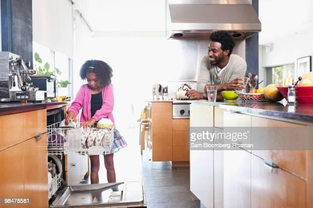 Father watching daughter loading dishwasher