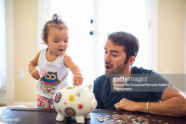 Father watching daughter put coins in piggy-bank