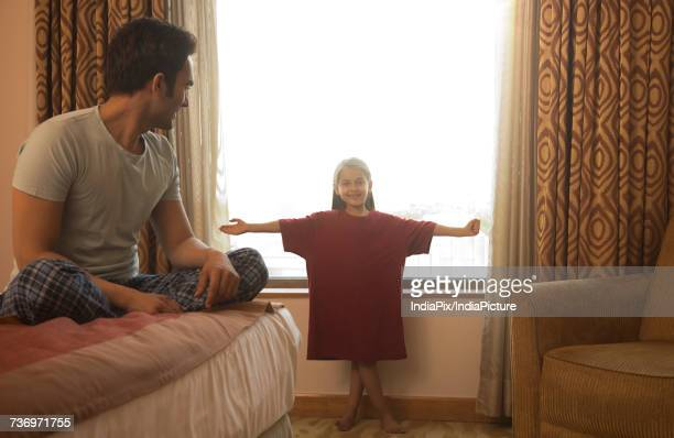 Father watching daughter try on his t-shirt in bedroom