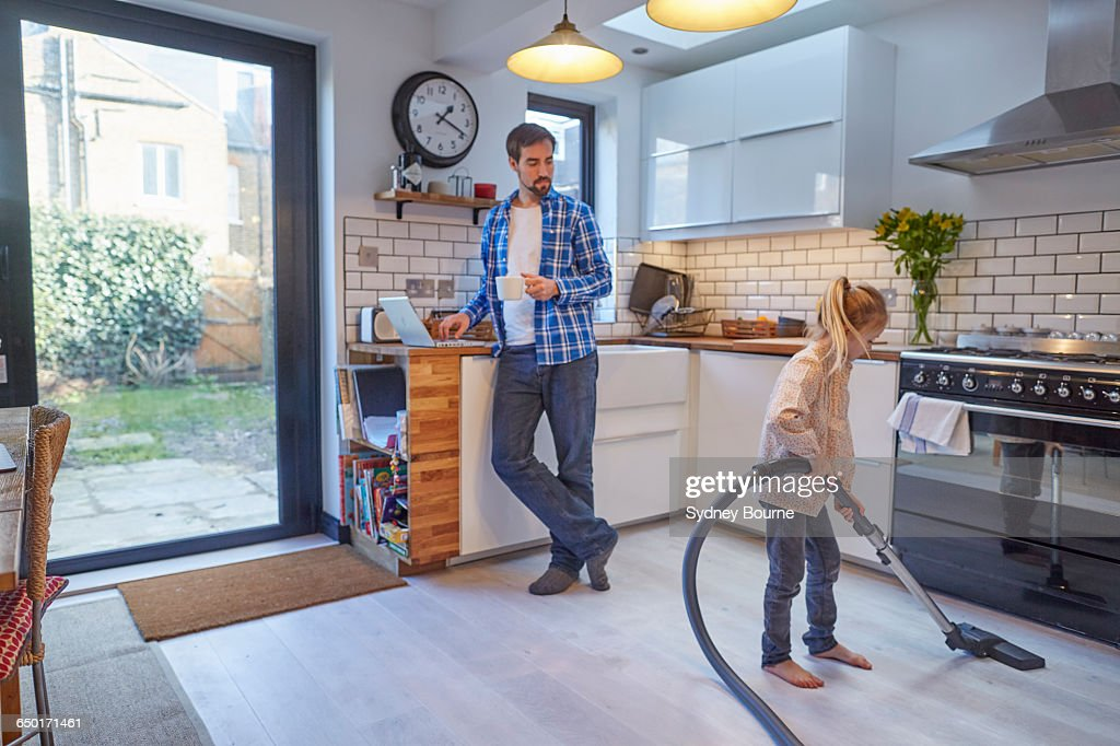 Father Watching Daughter Vacuum Kitchen Floor Stock Photo   Getty Images