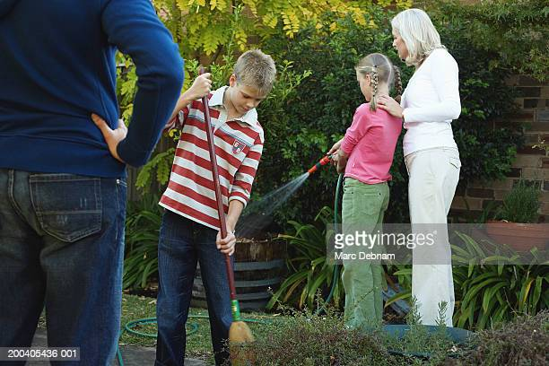Father watching family gardening, hand on hip, mid section, rear view