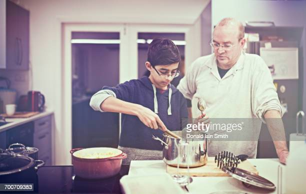 Father watching son cooking in kitchen
