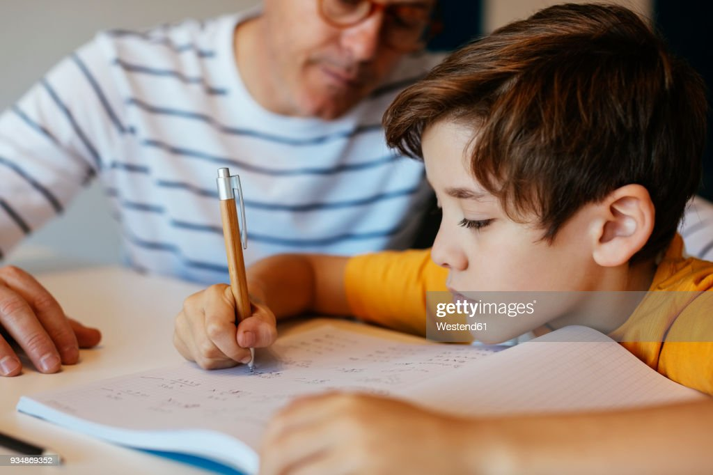 Father watching son doing homework at table : Stock Photo