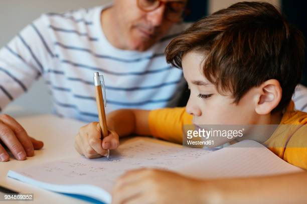 father watching son doing homework at table - homeschool ストックフォトと画像