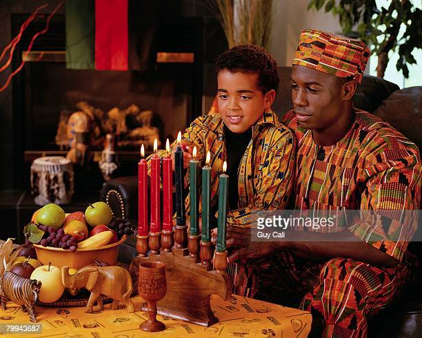 father watching son light candles - kwanzaa stock pictures, royalty-free photos & images