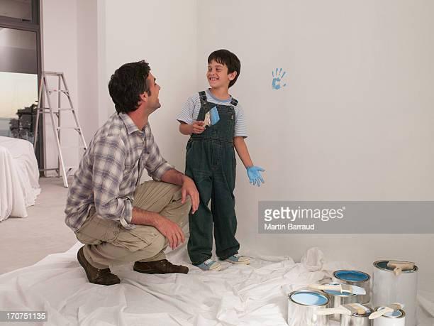 Père en regardant son fils de faire de la peinture sur le mur avec Empreinte de main