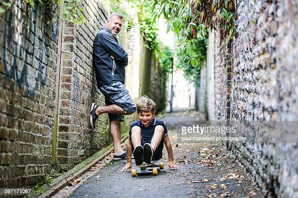 Father watching son on skateboard