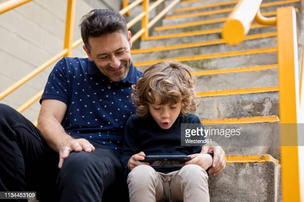 father watching son playing with handheld game console - handheld video game stock pictures, royalty-free photos & images