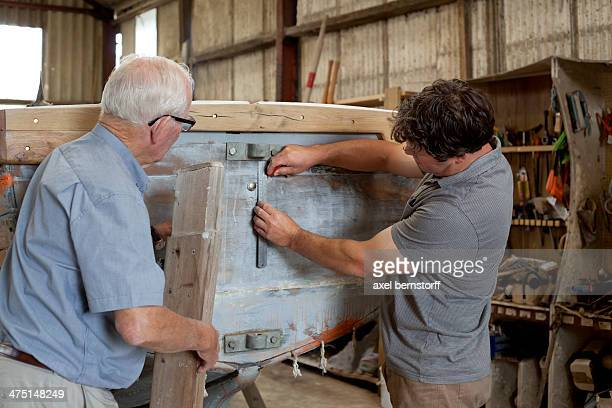 Father watching son restore boat in workshop