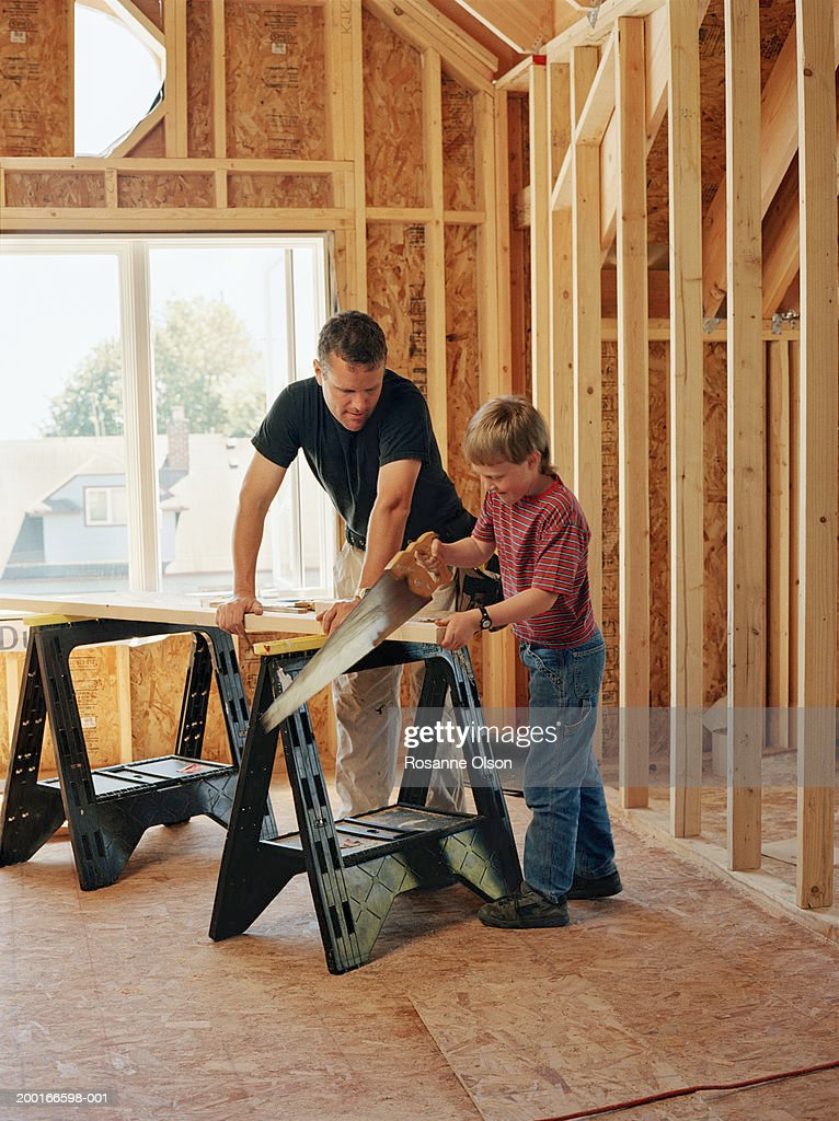 Father watching son (8-10) saw piece of wood on sawhorse : Stock Photo