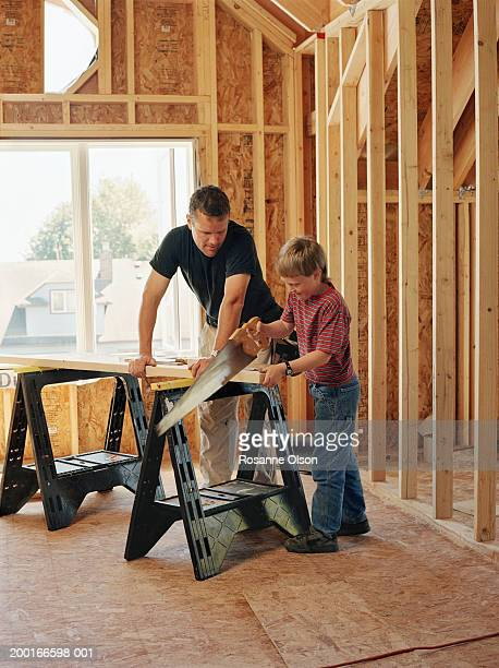Father watching son (8-10) saw piece of wood on sawhorse