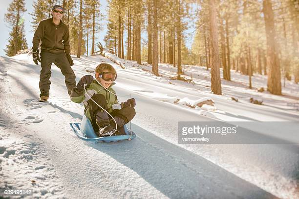 Father watching son sled down a hill