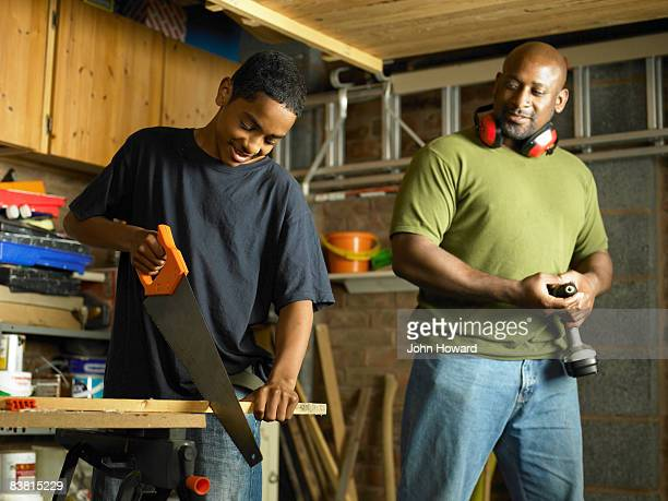 Father watching teenage Son sawing wood