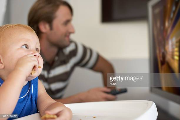 Father Watching Television While His Son Looks On