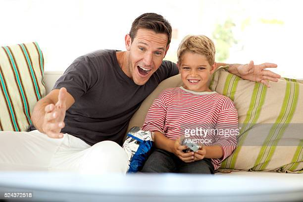 father watching tv with son - changing channels stock photos and pictures