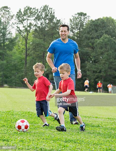 Father watching twin sons play soccer