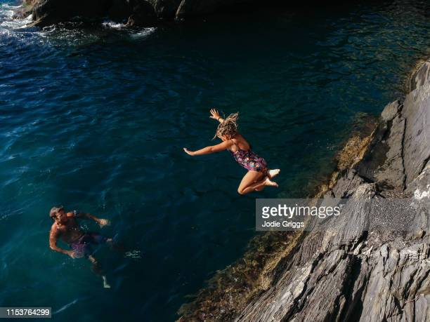 father watching young girl jumping off a rock into the ocean - moed stockfoto's en -beelden