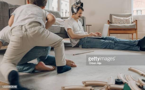 vader die een helm draagt die van huis probeert te werken - werk privé balans stockfoto's en -beelden