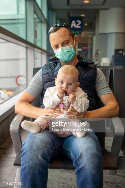 father wearing mask sitting with daughter at airport - toddler at airport stock pictures, royalty-free photos & images